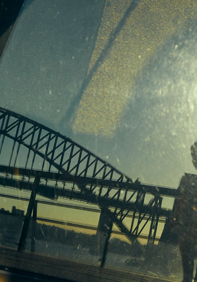A view of part of the Sydney Harbour Bridge and a silhouette of a person from behind tinted glass.