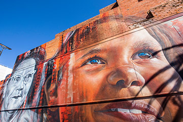 A realistic mural of an indigenous child on the side of a building.