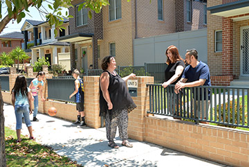 A suburban street view of neighbours chatting, with children playing on the footpath nearby.