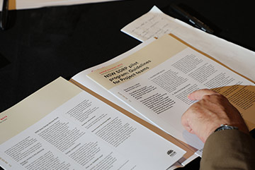 A view of a person's finger pointing at a document on a table in front of them.