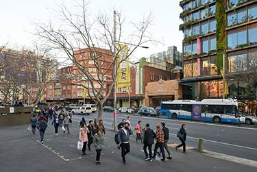 A view of Central Park on Broadway in Sydney with pedestrians passing by.
