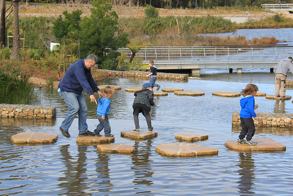 A family crossing a waterway across stepping stones.