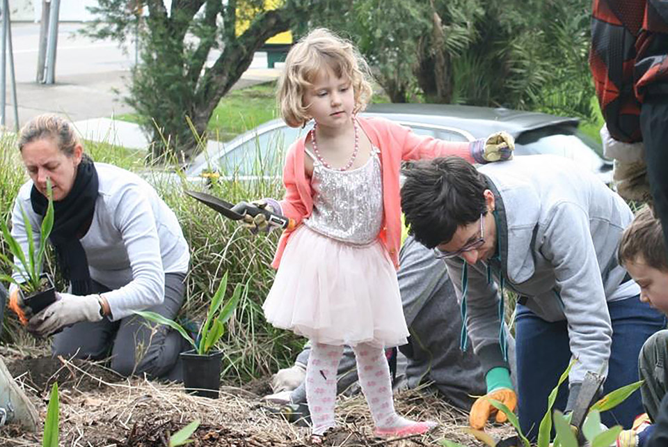 Community residents helping to plant plants in a community garden. A child stands with gardening gloves and a spade in her hands.