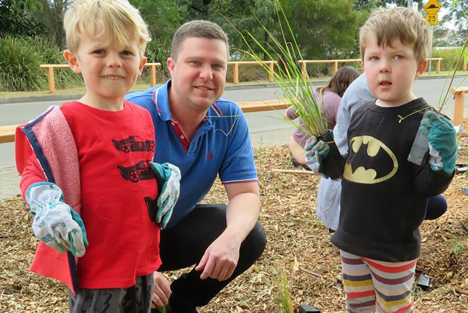 A man, squatting in between 2 toddlers with gardening gloves on near a woman gardening in a community garden.